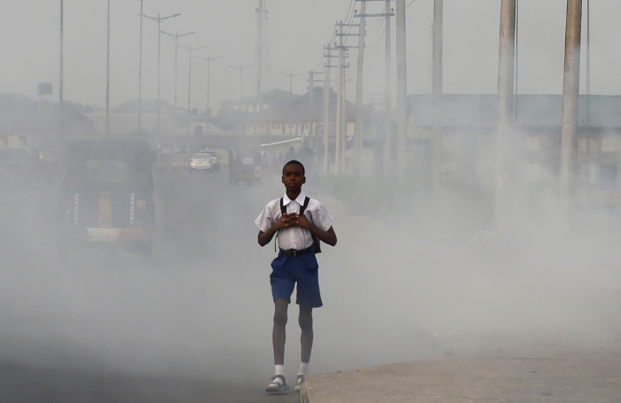 """A school boy walks past smokeand fumes emitted from a dump in the city of Port Harcourt, Rivers State, on February 14, 2017.  The Nigerian city of Port Harcourt used to be known as """"The Garden City"""" because of its soaring palm trees and green open spaces. But the description, even if could be applied after decades of development linked to the oil industry, has hardly seemed appropriate in the last few months. Since late last year, black soot has been falling from the sky, scaring and angering residents who claim nothing is being done to protect their health.  / AFP / PIUS UTOMI EKPEI        (Photo credit should read PIUS UTOMI EKPEI/AFP/Getty Images)"""